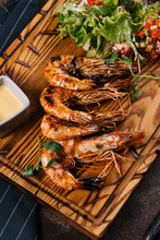 High Angle View Of Grilled Shrimps Served With Salad On Wooden Board