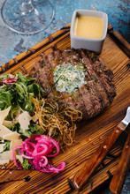 High Angle View Of Grilled Beef With Salad And Dip Served On Wooden Board