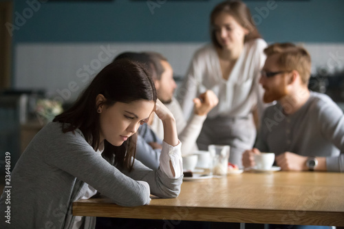 Fotografia  Upset young girl sit alone at coffee table in cafe feeling lonely or offended, s