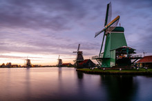 Traditional Windmills By Canal Against Cloudy Sky During Sunset