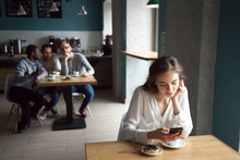 Diverse Young Guys Interested With Beautiful Girl Sitting At Near Table Using Smartphone, Enjoying Coffee In Cafe, Curious Males Looking At Pretty Female, Liking Or Falling In Love From First Sight