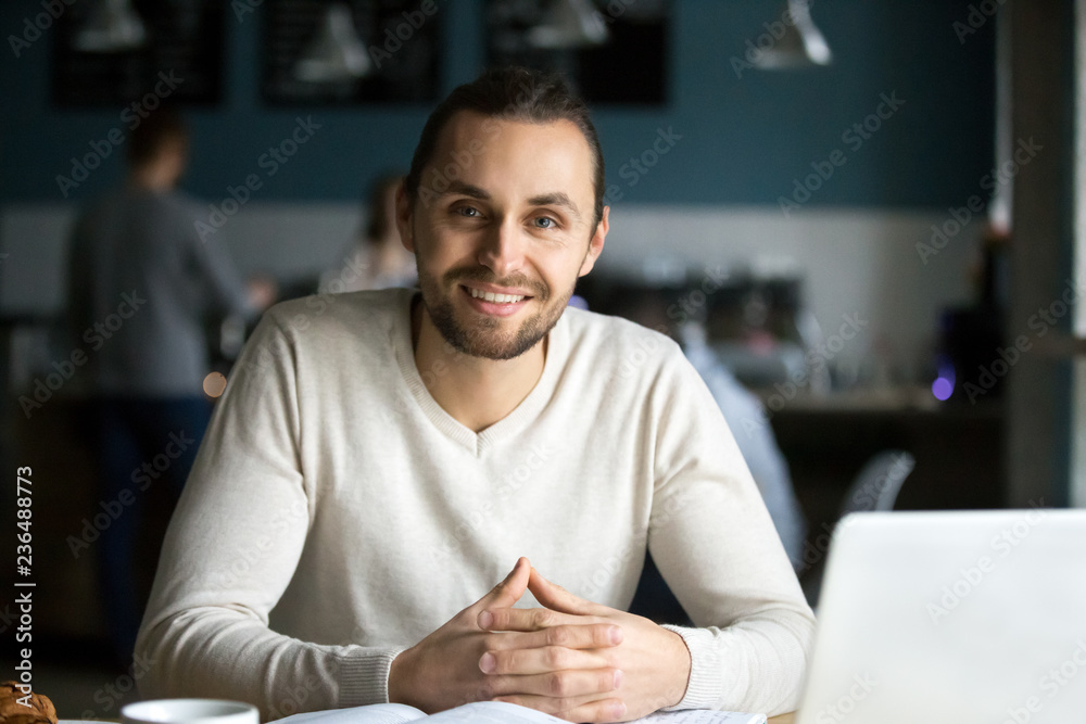 Fototapeta Portrait of smiling millennial man sitting in cafe with laptop and books on table, happy young guy work in coffeeshop using computer, male student look at camera busy preparing report in coffeehouse