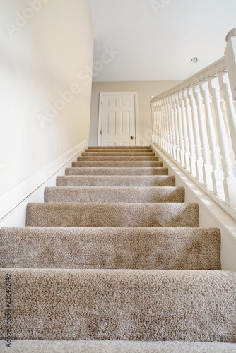 Photo Ascending Carpeted Open Staircase in Neutral Colors
