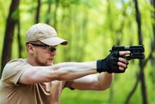 Instructor With Gun In Forest Leads Aiming And Posing On Camera