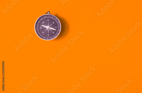 Valokuva Black compass on orange background, equipment for travel, tourism and business,