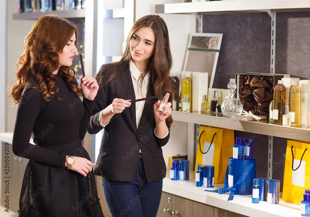 Fototapety, obrazy: polite female consultant helping customer with choice in cosmetics store.