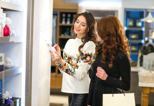 Obraz polite female consultant helping customer with choice in cosmetics store. - fototapety do salonu