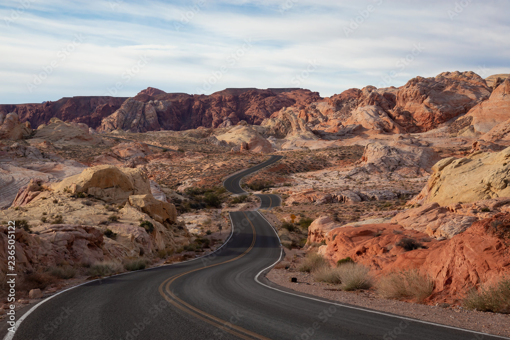 Fototapeta Scenic view on the road in the desert during a cloudy and sunny day. Taken in Valley of Fire State Park, Nevada, United States.