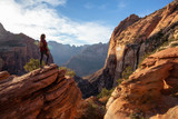 Adventurous Girl at the edge of a cliff is looking at a beautiful landscape view in the Canyon during a vibrant sunset. Taken in Zion National Park, Utah, United States.