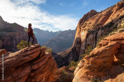 Adventurous Girl at the edge of a cliff is looking at a beautiful landscape view in the Canyon during a vibrant sunset Fototapete