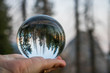 Sunset over Mountains with Forest and Moon Captured in Glass Ball Held in Palm