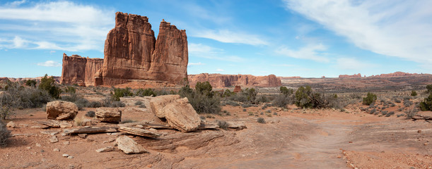 Panoramic landscape view of beautiful red rock canyon formations during a vibrant sunny day. Taken in Arches National Park, located near Moab, Utah, United States.