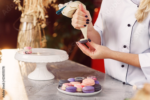Aluminium Prints Macarons Close up baker hands with confectionery bag squeezing cream to macarons shells.