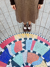 Closeup Of Woman Standing By Mosaic In Sidewalk