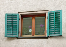 European Window With Green Shutters And Blooming Orchid Plant