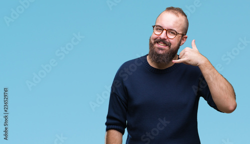 Fotografie, Obraz  Young caucasian hipster man wearing sunglasses over isolated background smiling doing phone gesture with hand and fingers like talking on the telephone