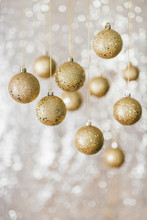 Golden Baubles Against Shiny B...