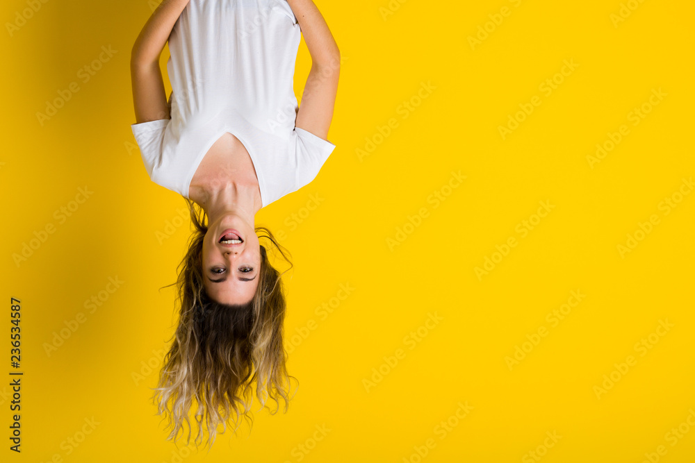 Fototapeta Beautiful young blonde woman jumping happy and excited hanging upside down over isolated yellow background