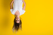 Leinwandbild Motiv Beautiful young blonde woman jumping happy and excited hanging upside down over isolated yellow background