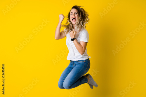 Fotografía  Beautiful young blonde woman jumping happy and celebrating with raised hands and