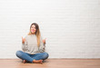Young adult woman sitting on the floor over white brick wall at home success sign doing positive gesture with hand, thumbs up smiling and happy. Looking at the camera with cheerful expression