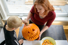 Mother And Son Looking At The Halloween Jack-o-lantern They Made