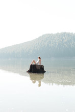 Woman Sits On A Tree Stump In The Water