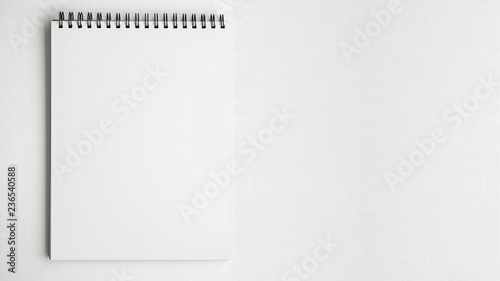 Photo Blank pape notepad on white table background.