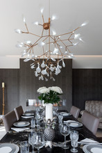 Black Granite Dining Table Set For Dinner With Large Ceiling Lamp Above.
