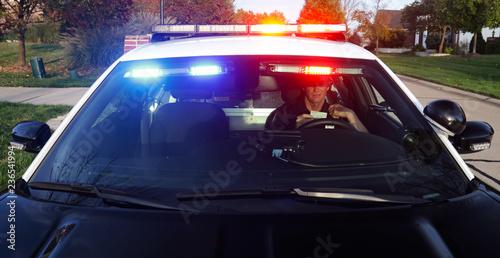 Obraz na plátně Police: Officer Calls In License From Inside Patrol Car