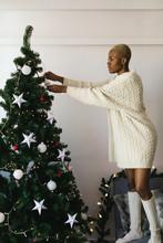 Closeup Of A Latin Woman Decorating Christmas Tree At Home.
