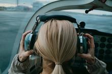 Female Pilot Putting On Headset