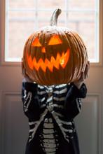 Boy In Skeleton Shirt Holds A Glowing Halloween Jack-o-lantern U
