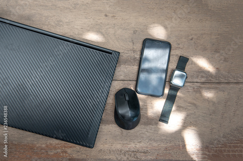 note book with smart phone and digital watch on wood table
