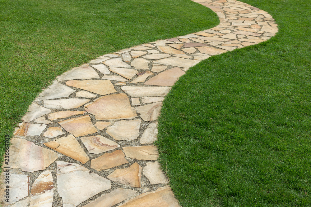 Fototapeta Stone path on green grass in the garden
