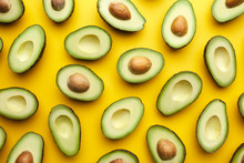Exotic Halved Avocados On Yellow Background.