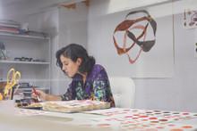 Female Artist Making Illustrations At Table