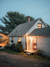 A Cozy Cottage In Maine At Dusk.