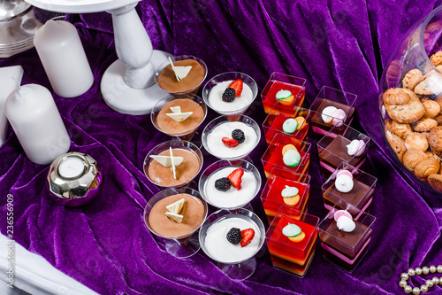 Candy bar. Wedding reception table with sweets, candies, dessert, meringues, fruit tart, cupcakes, muffins, cakes, eclairs