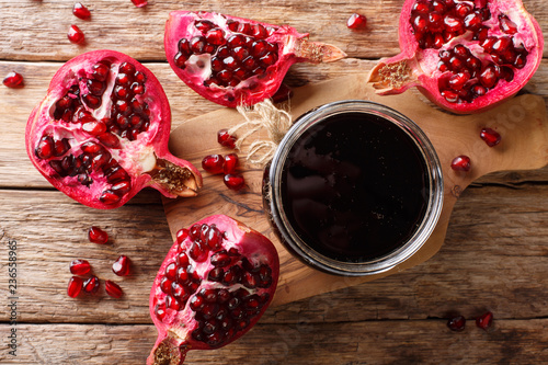 Fotobehang Aromatische Narsharab sauce is a condensed pomegranate juice with spices in a glass jar close-up. horizontal top view