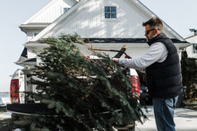 Man Trimming The Trunk Of A Christmas Tree In The Driveway Of His Home