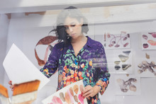 Female Artist Looking At Illustrations On Papers In Studio