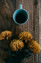 Blue Cup Of Coffee On A Wooden Table Close To Yellow Flowers