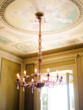 Beautiful Chandelier Hanging From Ornamental Ceiling