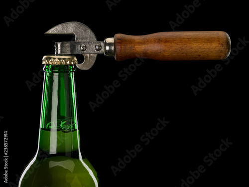 Staande foto Bier / Cider Neck of glass bottle with beer and can opener
