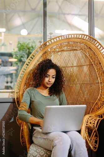 Young woman with laptop in armchair