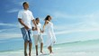 Healthy African American parents and son wearing white clothing holding hands and chilling on beach vacation RED EPIC