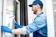 Man as a professional cleaner in blue uniform washing window with rubber brush indoors
