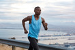 Leinwanddruck Bild - Outside shot of confident Afro American fitness male has goal achievement challenge to reach destination without break, works actively with hands, dressed in sportswear, joggs over nice nature view
