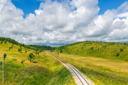 Poster Onweer Railroad and countryside scenery with green hills and blue sky